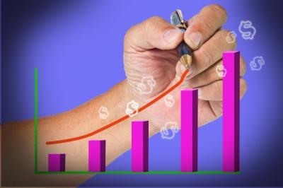 A hand drawing a line upwards along a bar graph.