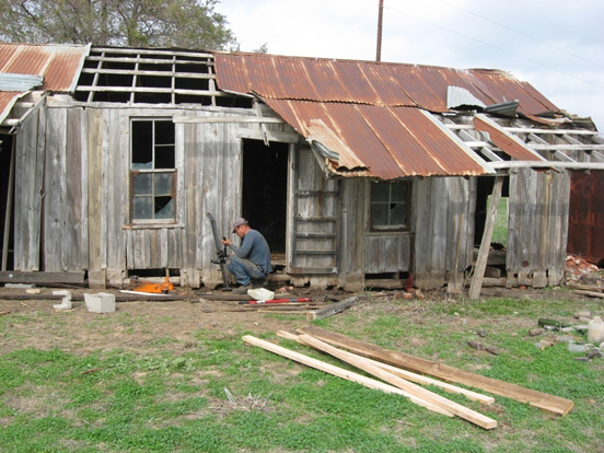 Man works to restore dilapidated cabin.