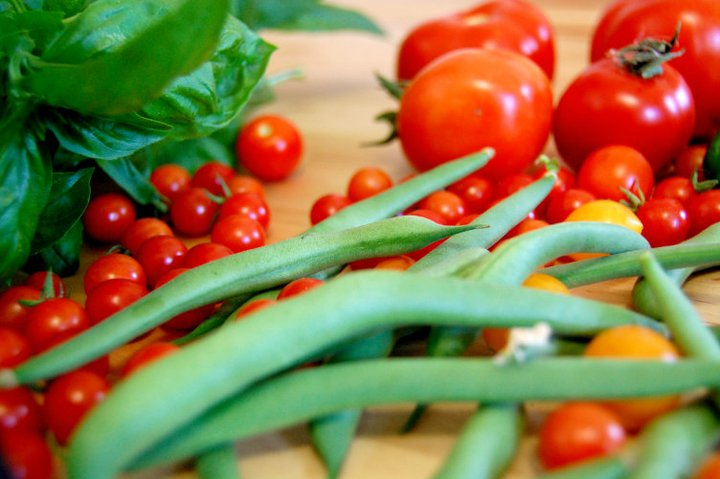 A stack of tomatoes, radishes, beans and other vegetables.