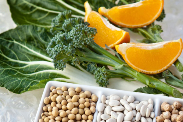 Broccoli florets, orange slices, spinach leaves, soybeans, chickpeas