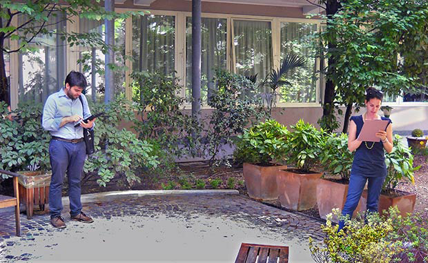 Two students write on clipboards in a large garden space.
