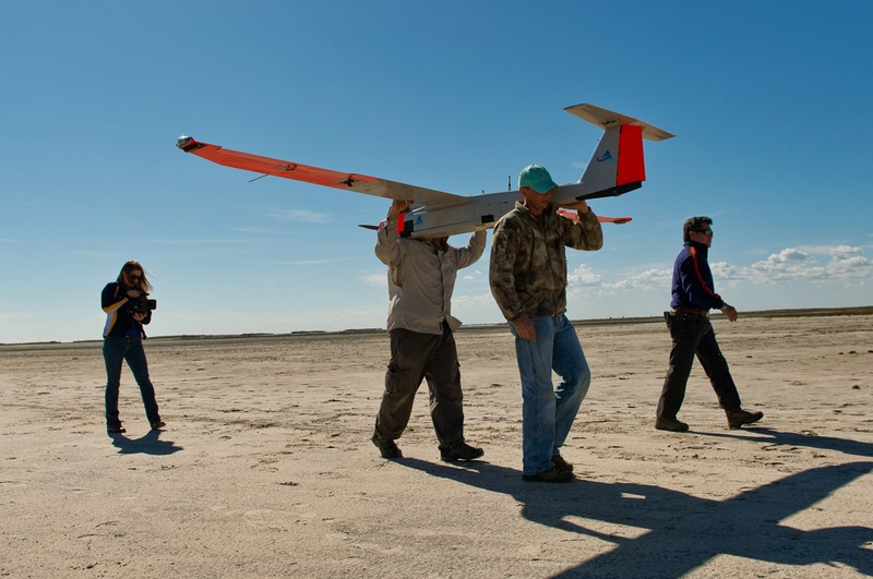 two men carry a drone plane on their shoulders across a dry, barren field