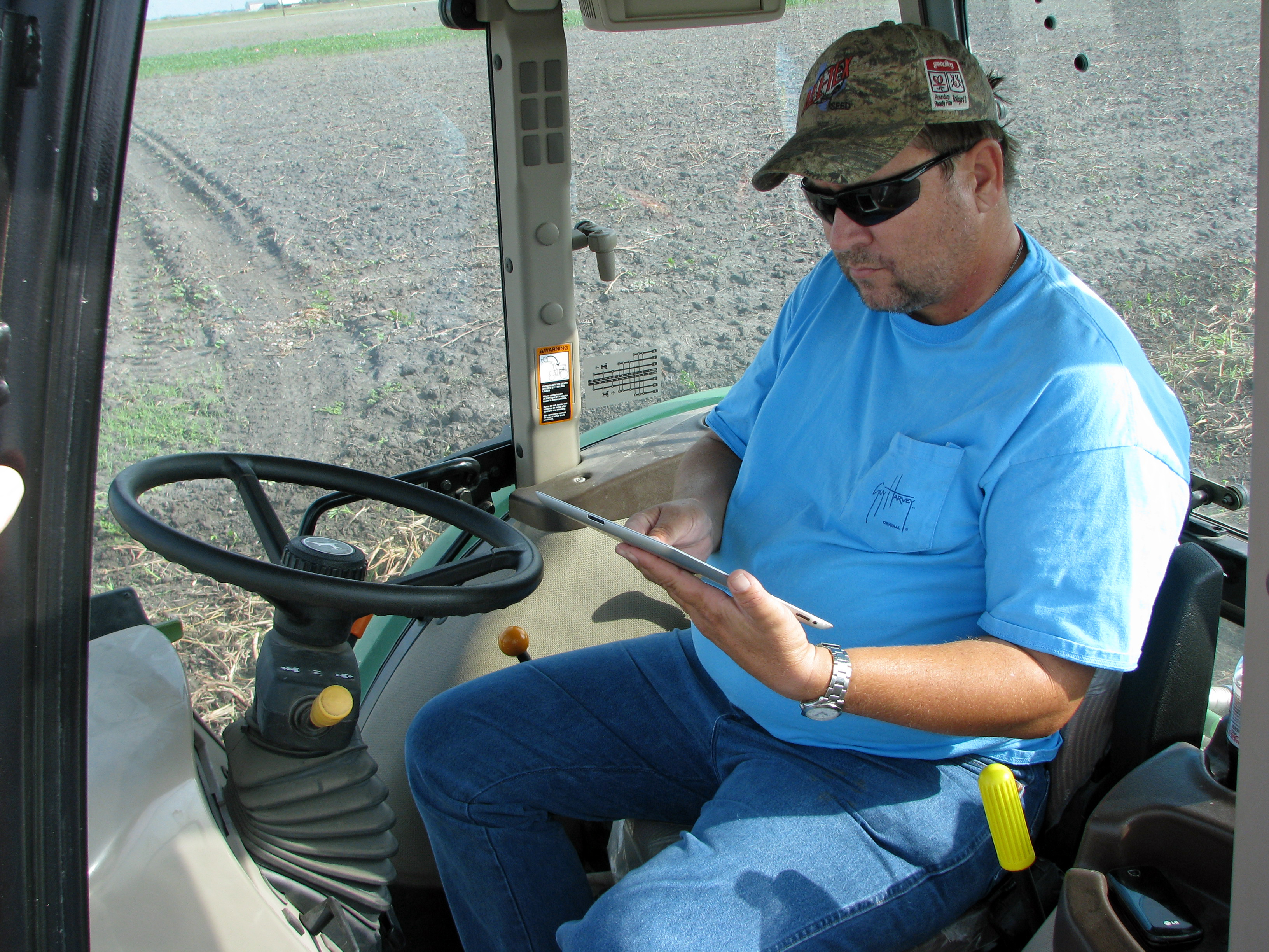 Farmer on tractor works with iPad