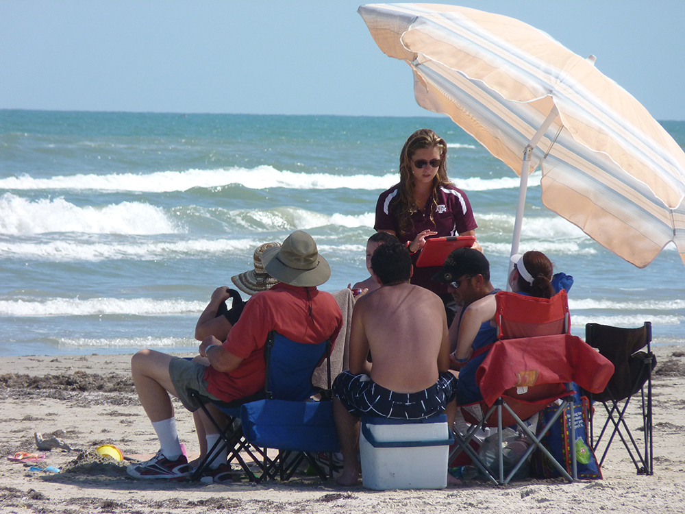 Woman talks to group of people on a beach under an umbrella
