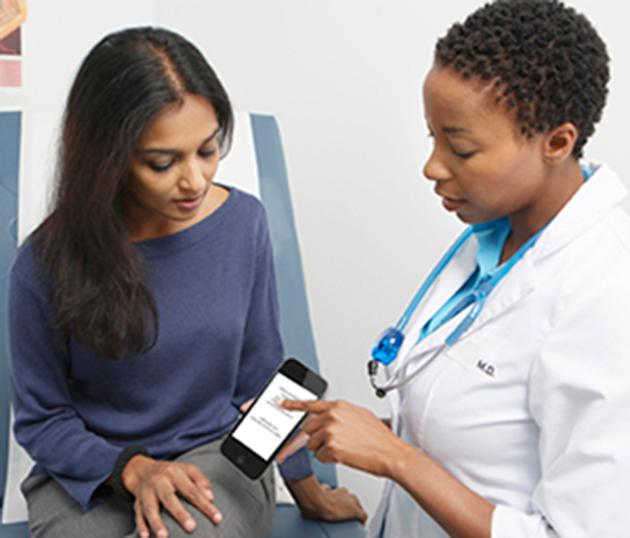Doctor demonstrates small touchscreen device to patient