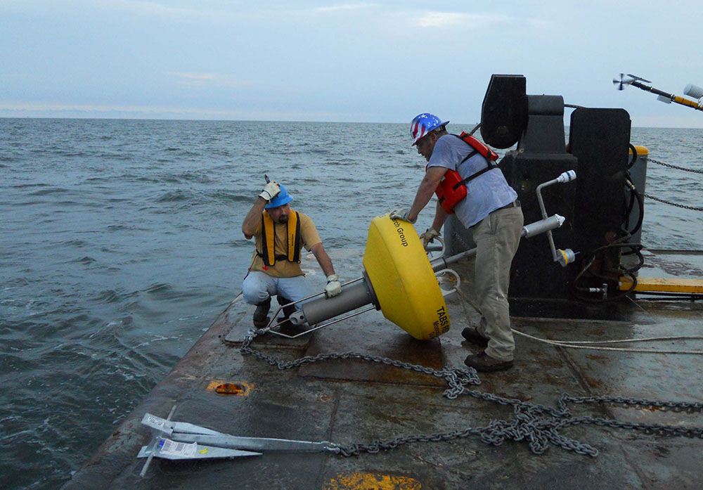 Workers lower buoy into ocean.