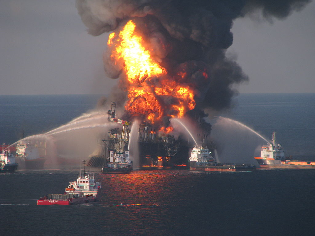 Firefighting boats spray water on ocean drilling platform that is burning