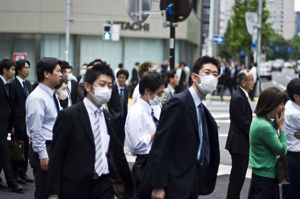 Men wearing surgical masks standing on city street corner