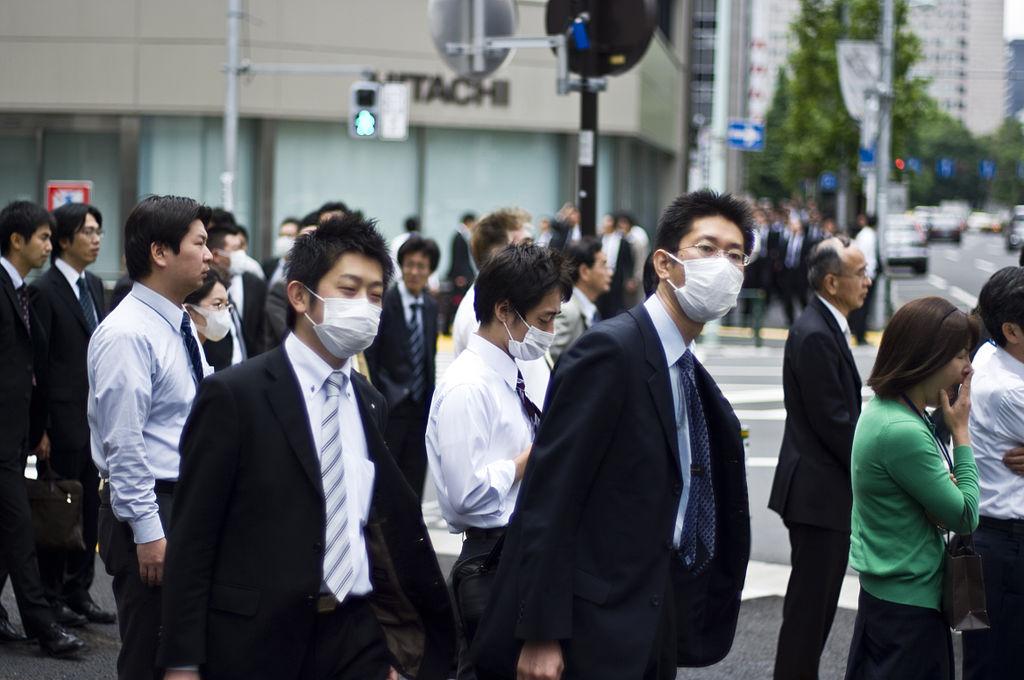 Men wearing surgical masks standing on city street corner