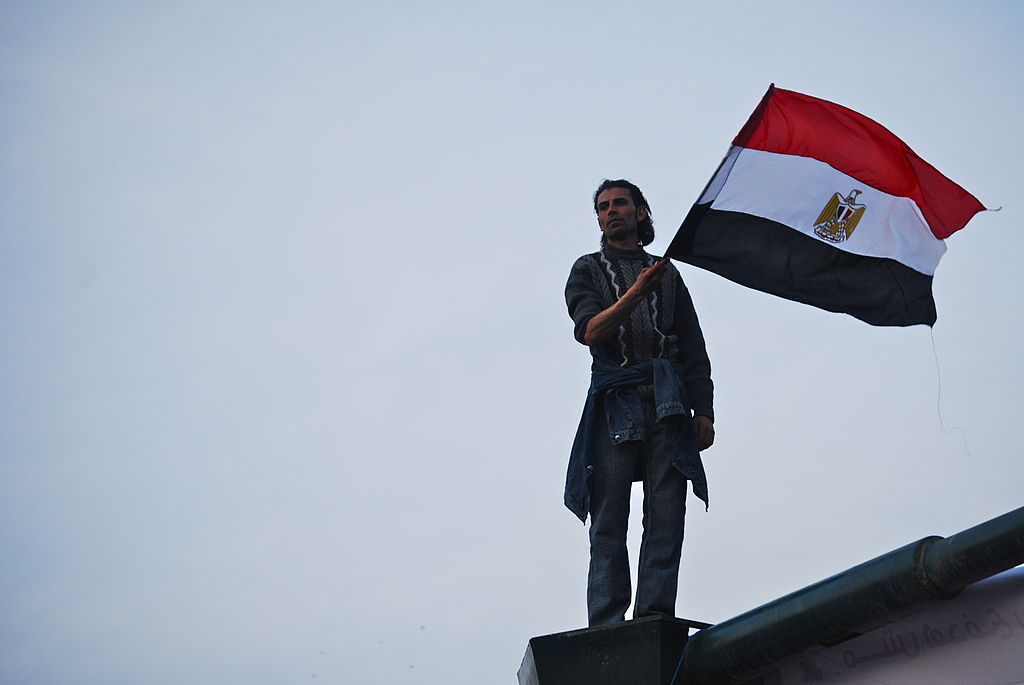 Man holds flag while standing on top of building