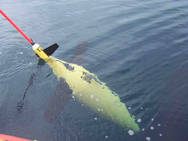 Ship lowers a ocean drone into the sea.