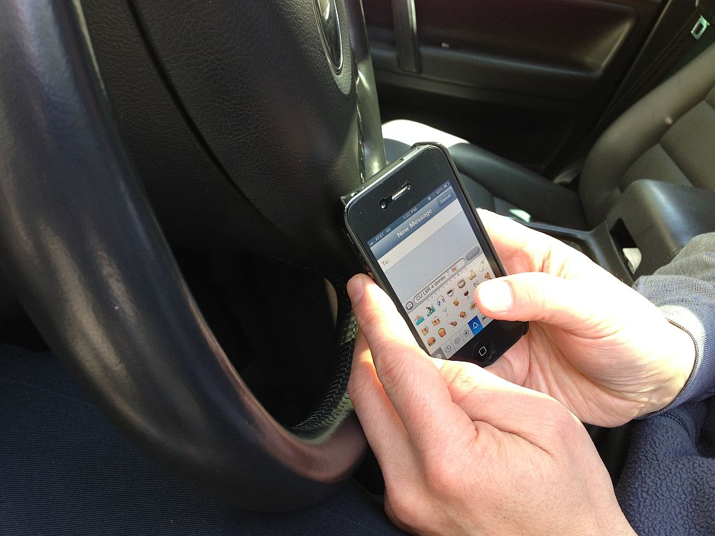 hands type on smartphone next to steering wheel of car