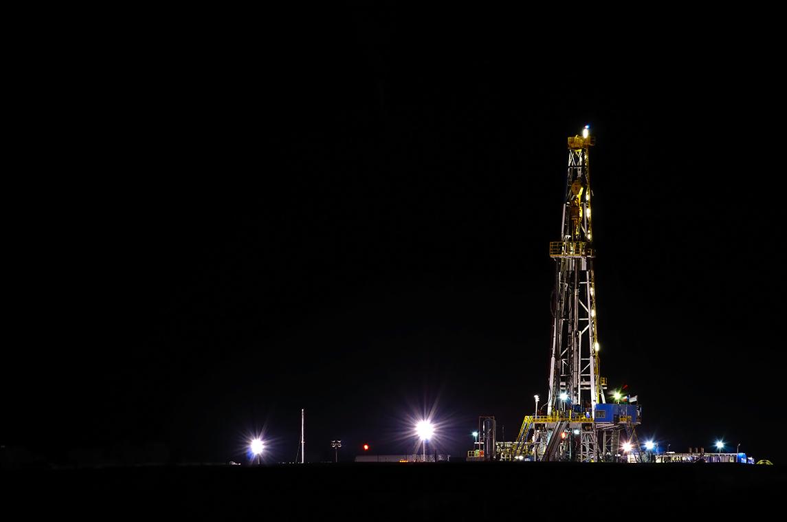 oil derrick lighted against dark sky