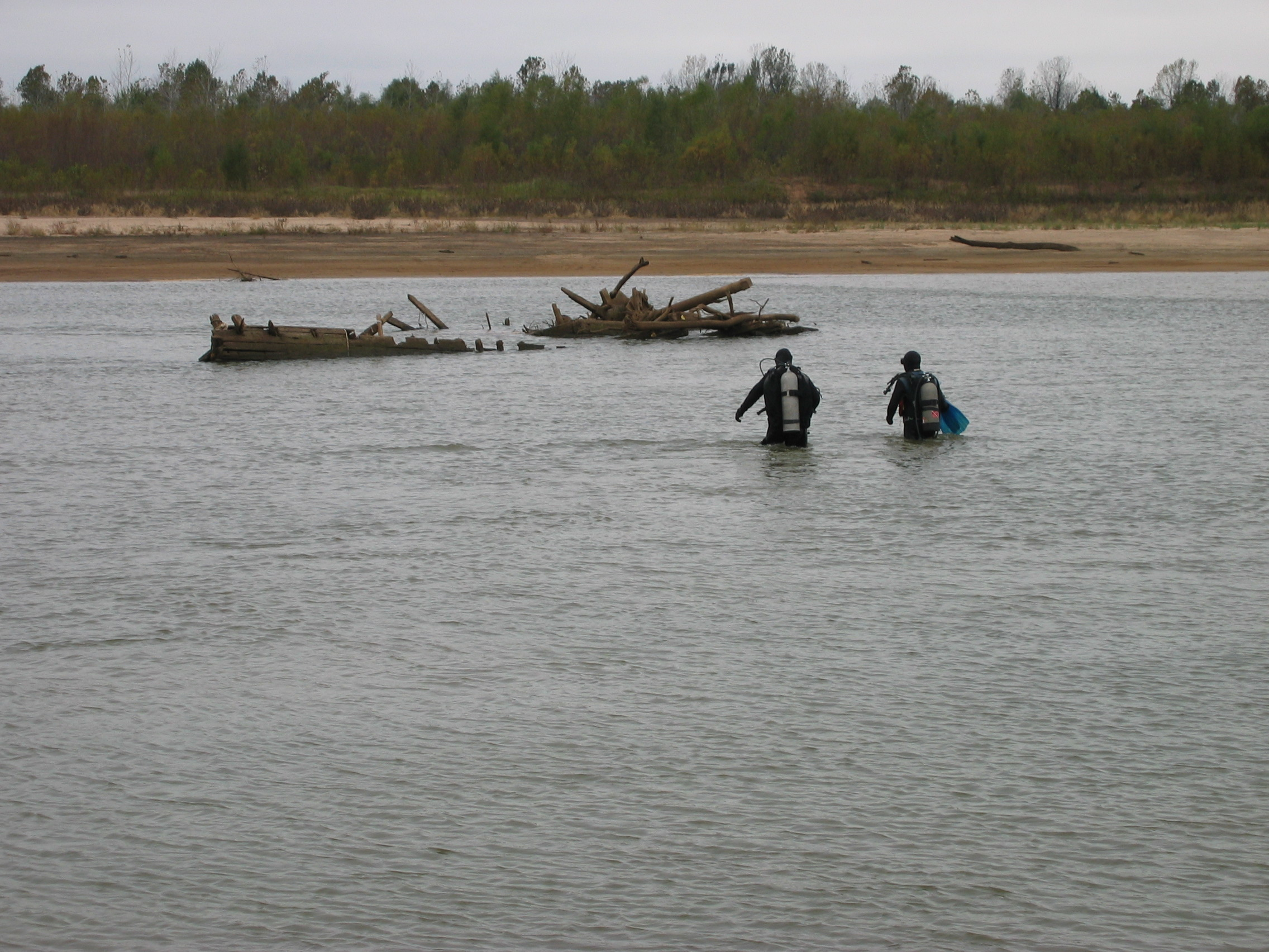 Two persons in SCUBA gear wade through shallow river water to reach a shipwreck