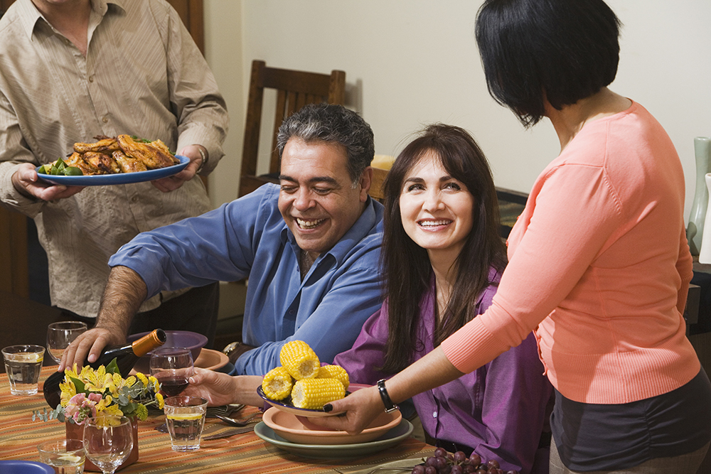 smiling people sit at dinner table with wine and food