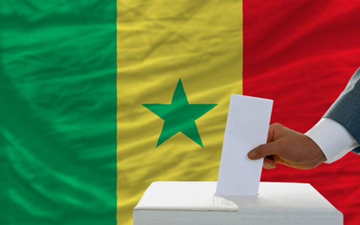 Hand places ballot into ballot box