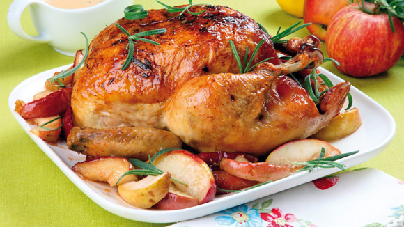 A whole, baked chicken on a platter with vegetables