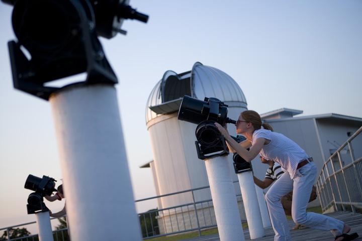woman looks at sky with binocular telescope