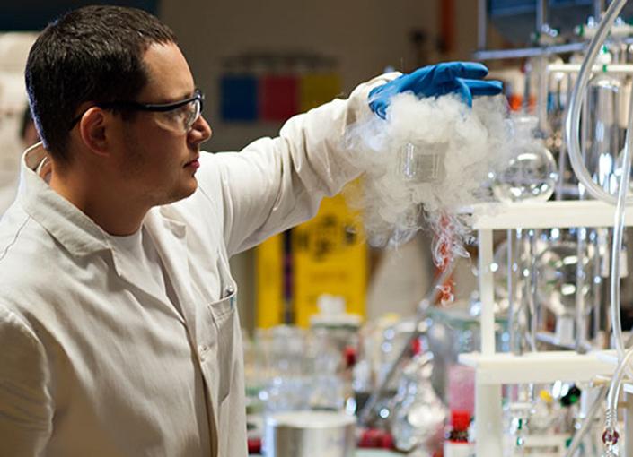 Chemist in laboratory watches vapor emerge from beaker