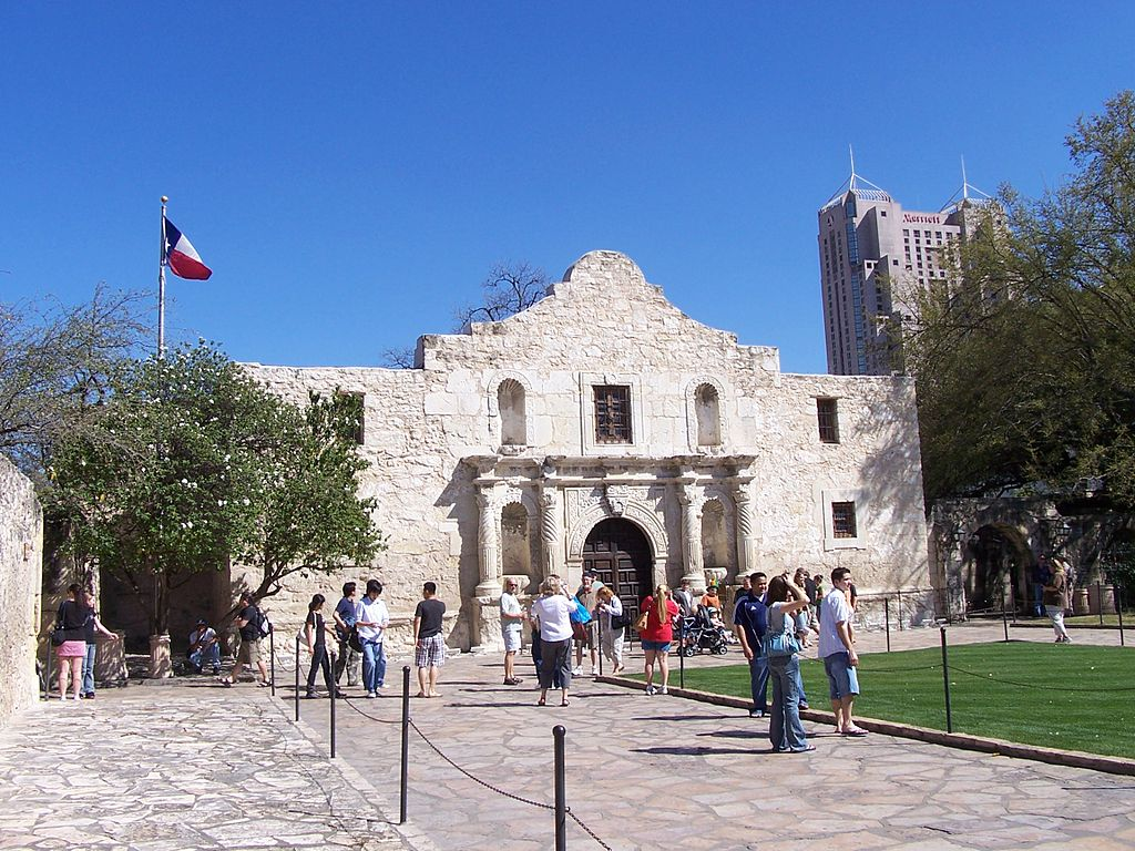 Tourists stand in from of the Alamo chapel