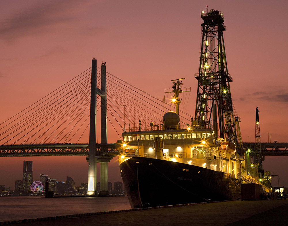A lighted ship in front of a bridge in twilight