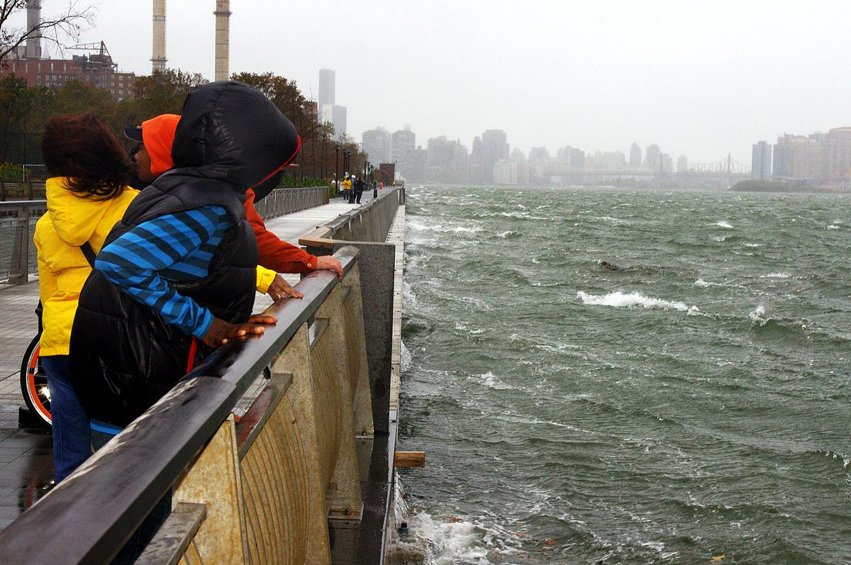 people line a bridge guardrail to watch storm surge