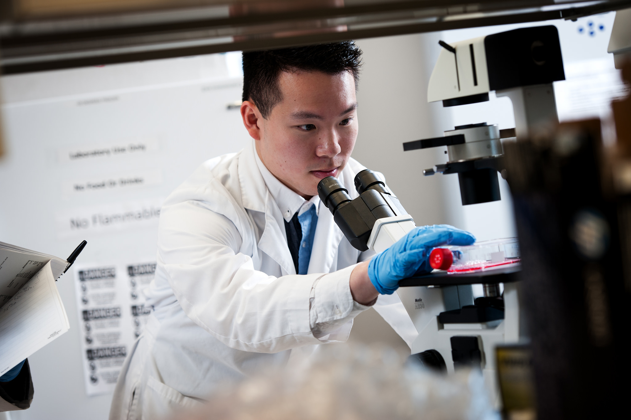 man in white lab coat works with a microscope