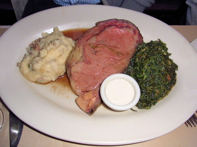plate of prime rib with potatoes and greens