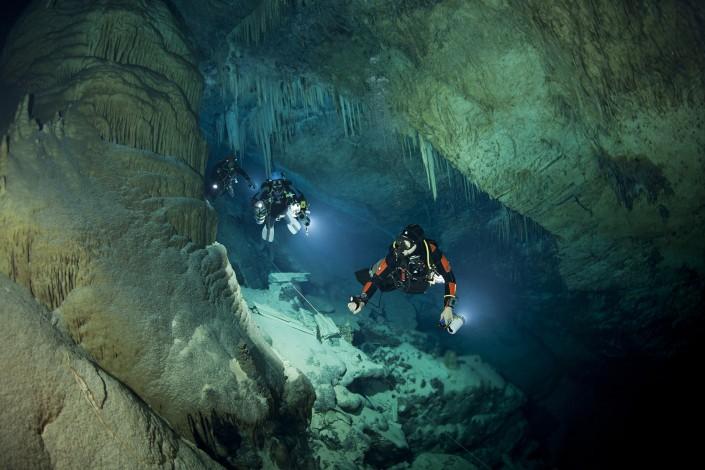 SCUBA divers explore underwater cave