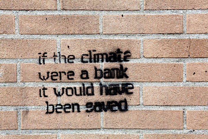 "graffiti on brick wall says ""If the climate were a bank, it would have been saved."""