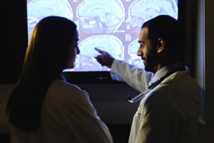 doctor and patient look at brain scans on light board