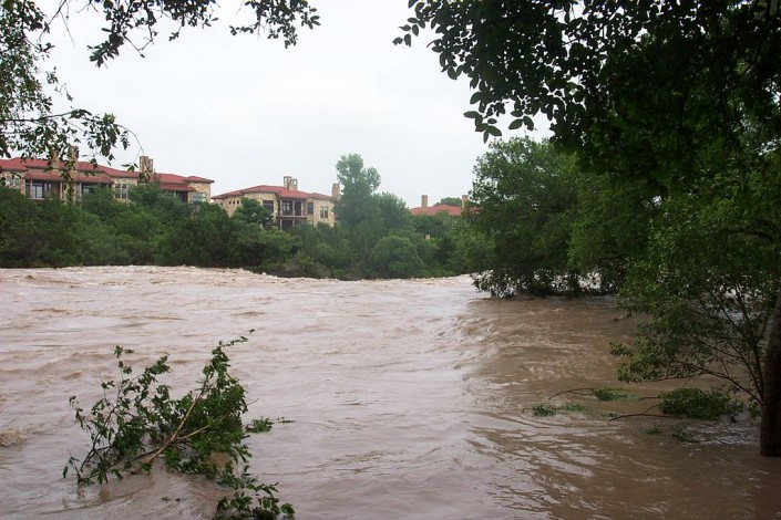flooding rivers runs behind apartment complex