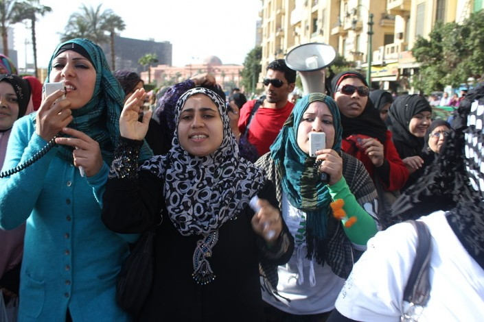 women participate in street protest with signs and megaphones