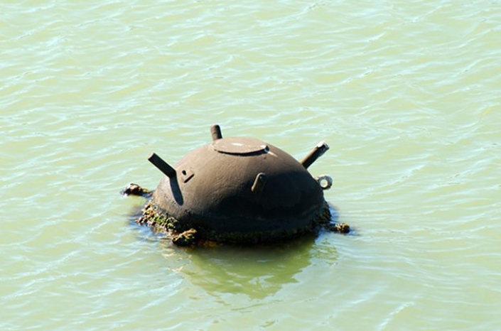 unexploded mine floats in ocean water