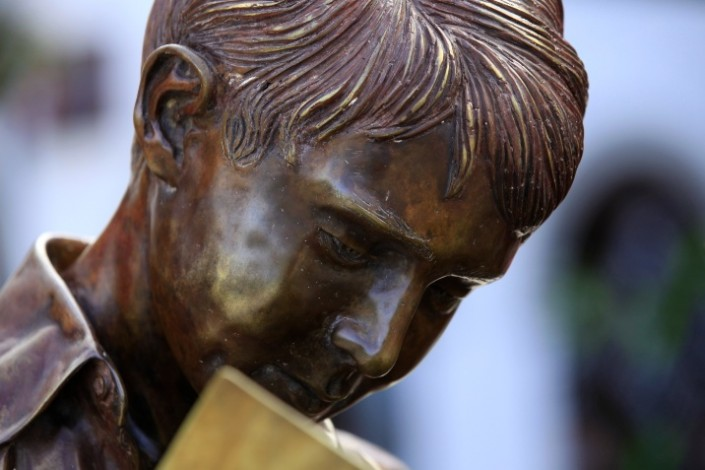 A statue of a boy reading a book
