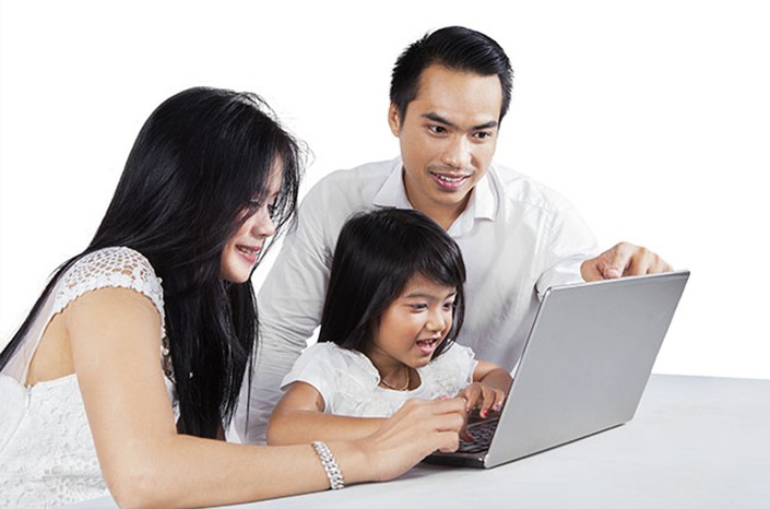 Parents look at laptop with young daughter between them