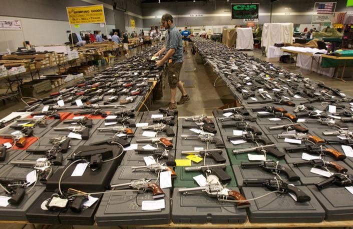 scores of handguns on display at gun show