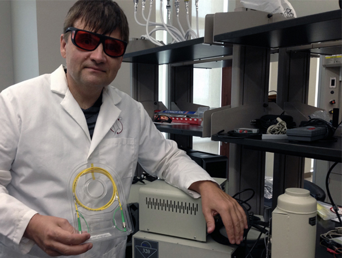 scientist in lab coat wearing protective eyewear