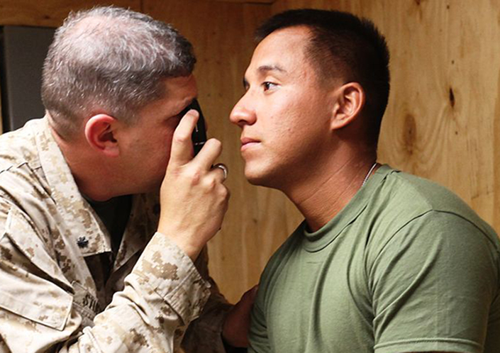 army doctor examines soldier's right eye