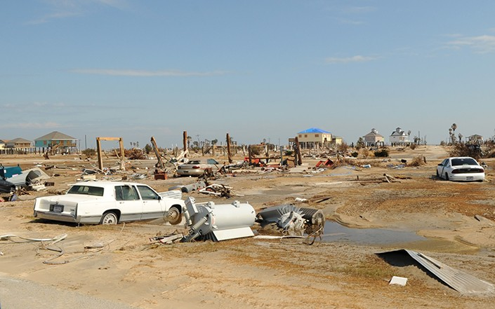 a landscape photo showing damaged homes, cars and equipment after hurricane
