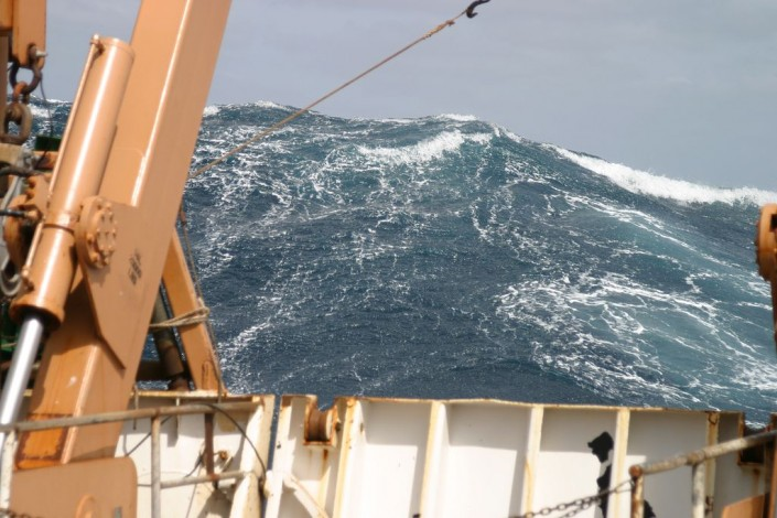 a monster wave approaches the bow of a ship
