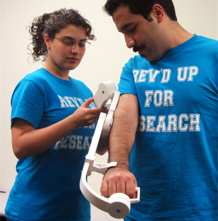 woman and man work with exoskeletal arm