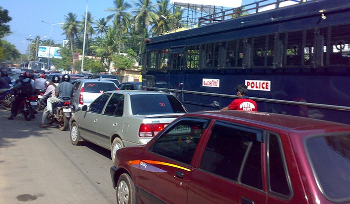 cars, buses and bicycles jam a traffic intersection