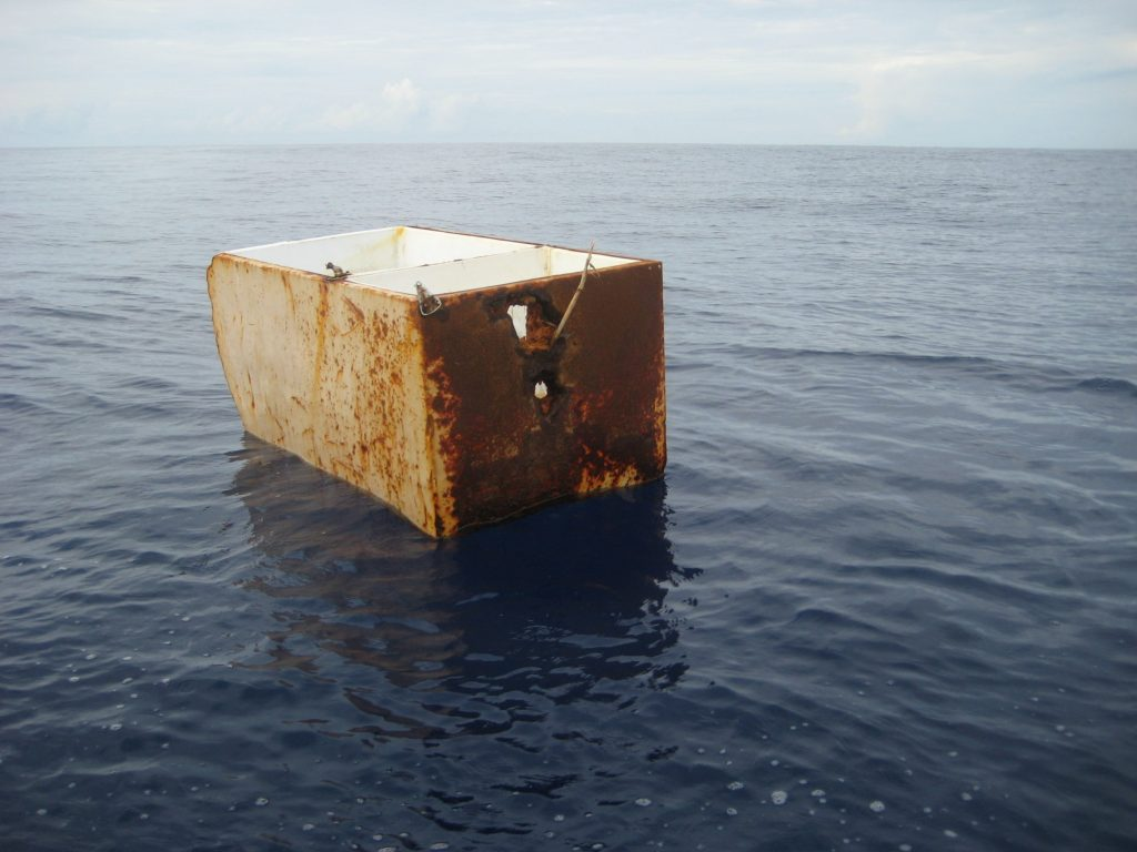 an abandoned refrigerator floats in a lakd
