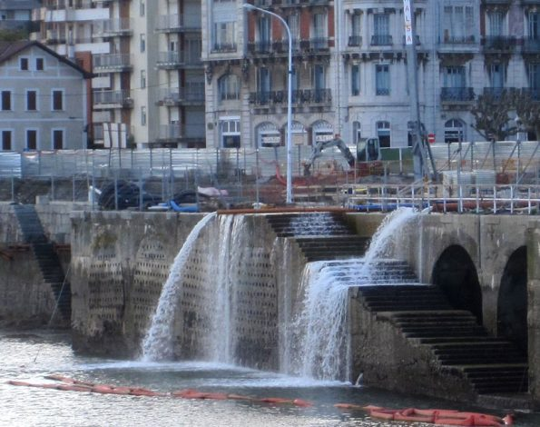 Water flows out of pipes and falls into a river.