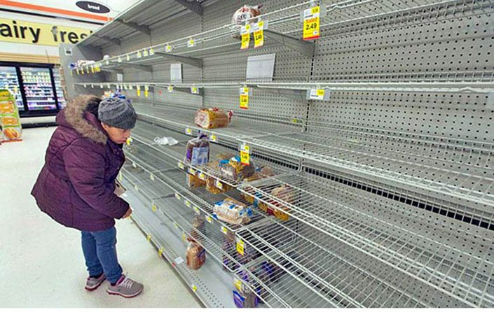 man looks at nearly empty bread shelves in grocery store