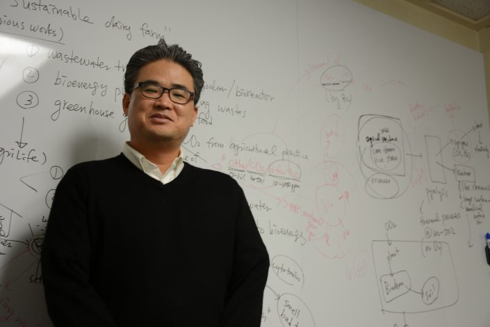 Professor stands in front of whiteboard filled with notes