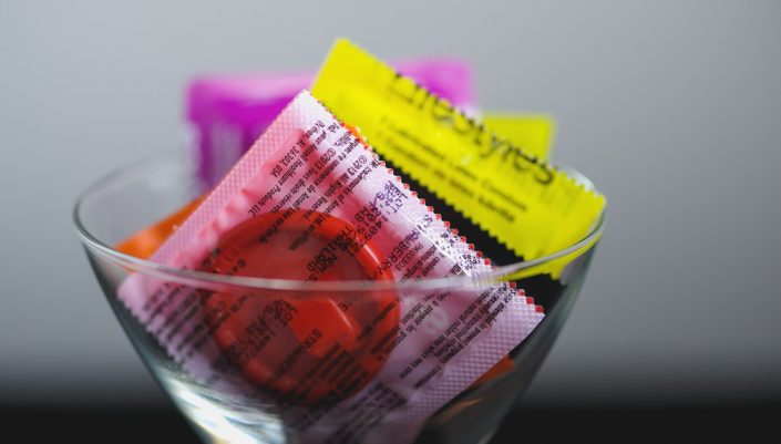 a small glass bowl filled with packaged condoms