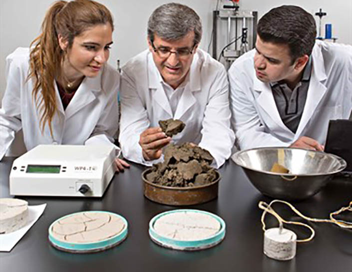 three scientists in lab coat examine rock-like materials