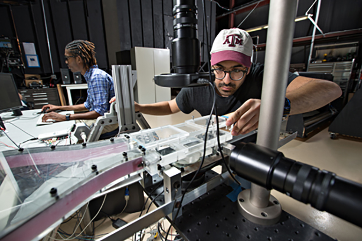 Young graduate student examines water droplets on material surfaces